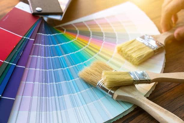 Pinceaux posés sur un nuancier de peinture pour la cuisine et la salle de bain